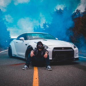 Man sitting by white car with blue smoke in the background